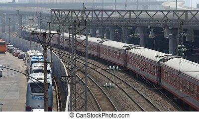 overlook train waiting on rail & locomotive fast passing.