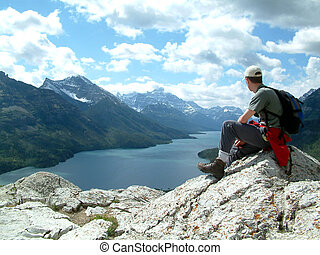 overlooking - Man sitting on top of mountain.