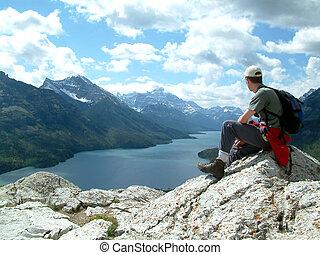 overlooking - Man sitting on top of mountain.