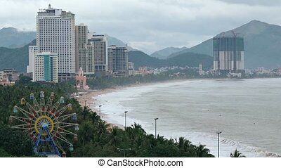 Overlooking vista of Nha Trang, Vietnam's coastline and cityscape, with highrise residential buildings, tropical palm trees and a Ferris wheel.