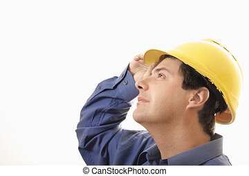Overseeing Progress - A man wearing hardhat looking upwards...