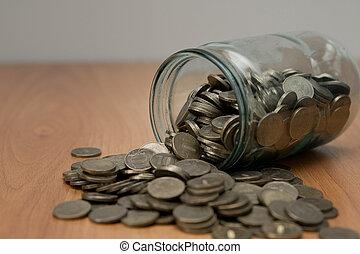 Overturned glass jar full of coins, money box