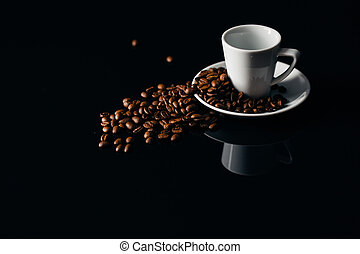 Overturned white mug with coffee beans