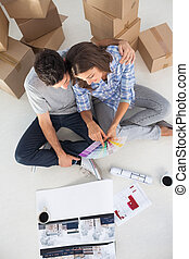 Overview of a man and his wife looking at house plans