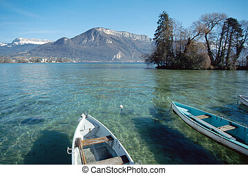 View of Annecy lake from the city, with small fishing boats, island and snowed mountains. Savoy, France in Europe