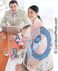Overview of cheerful colleagues looking at blue chart interface in a meeting