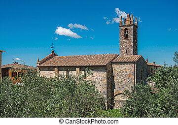 Overview of church and bell tower with trees around in the hamlet of Monteriggioni.