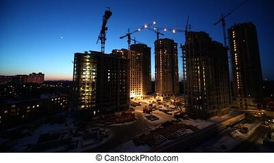 Overview of construction site in evening, time lapse
