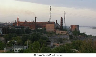 Overview of factory standing on riverbank, time lapse