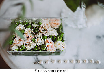 Overview of the wedding rings on a floral surface with roses and green blossom.
