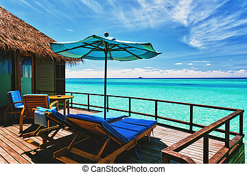 Overwater villa balcony overlooking tropical lagoon -...