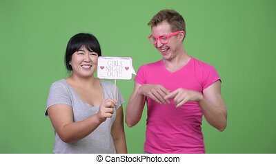 Overweight Asian woman and young gay man holding paper sign...