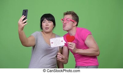 Overweight Asian woman and young gay man taking selfie...