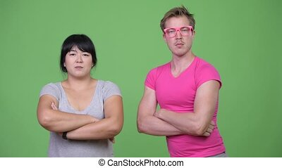 Overweight Asian woman and young gay man with arms crossed...