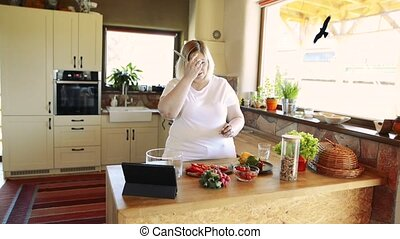 Overweight at home preparing salad in the kitchen. -...