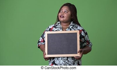 Overweight beautiful African woman against green background...