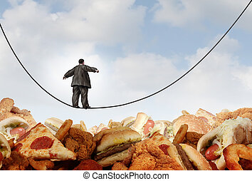 Overweight diet danger concept as an obese man walking on a tightrope high wire over mountains of greasy unhealthy junkfood as a metaphor for dieting risk and the challenges of eating disorders resulting in obesity.