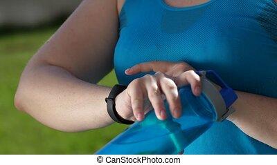 Overweight female runnner using fitness bracelet -...