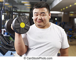 an overweight young man holding a dumbbell in fitness center.