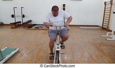 overweight man exercising on bike simulator