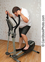 overweight man exercising on trainer