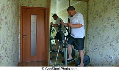 overweight man exercising on trainer ellipsoid - timelapse