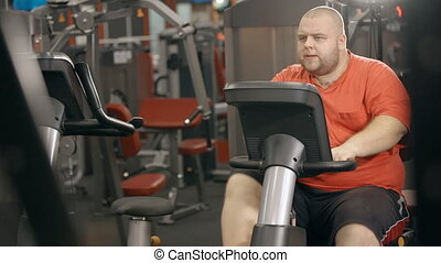 Overweight man is training on bicycle at fitness club.