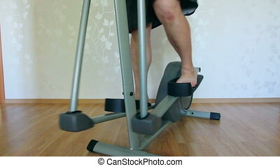 overweight man legs exercising on trainer ellipsoid