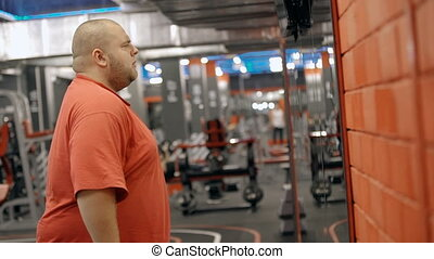 Overweight man looking at himself in the mirror -...
