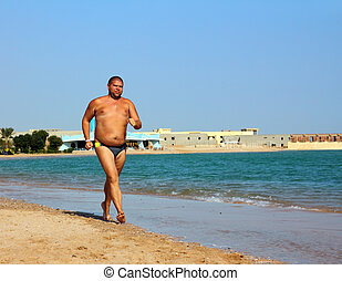 overweight man running on beach