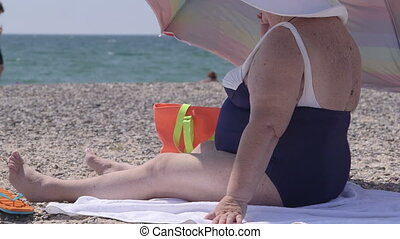 Overweight senior woman sitting on the beach