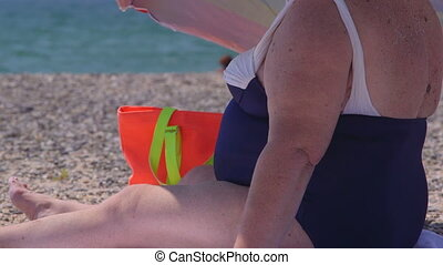 Overweight senior woman sitting on the beach