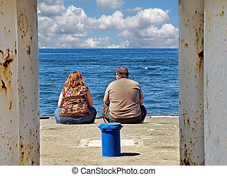 Overweight Watchers - Obese couple sitting at end of pier.