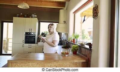 Overweight woman at home eating vegetable salad in the kitchen.
