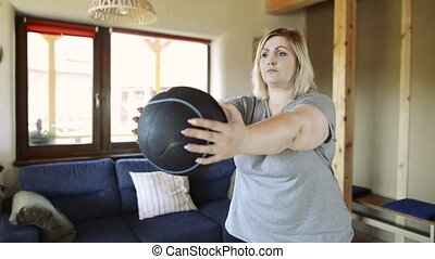 Overweight woman at home exercising with medicine ball.