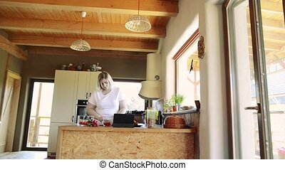 Overweight woman at home preparing vegetable salad in the kitchen.