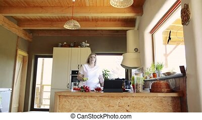 Overweight woman at home preparing vegetable salad in the...