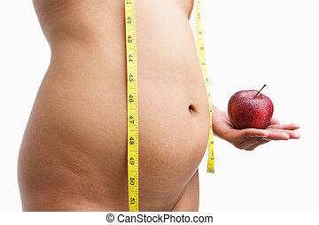 Overweight woman body holding apple with measuring tape