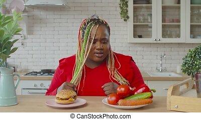 Overweight woman choosing between healthy and junk food - ...