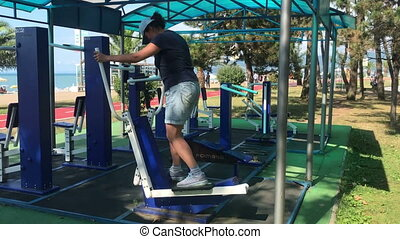 Overweight woman doing cardio exercises on ellipsoid at the gym outside in park