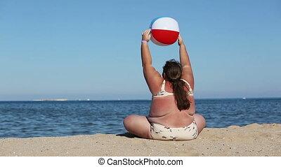 overweight woman doing gymnastics on beach
