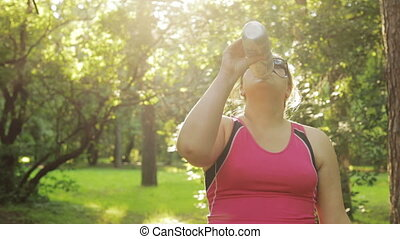 Overweight woman drinking water and starts running