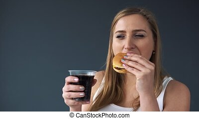 Overweight woman eating a hamburger and drinks a soda on the grey background. The camera moves downwards showing the process of eating to the bare belly