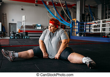 Overweight woman, exercises on the floor in gym