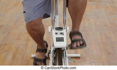 overweight woman exercising legs on bike simulator