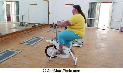 overweight woman exercising on bike