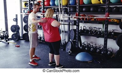 Overweight woman in gym training arms with trx fitness...