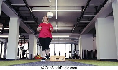 Overweight woman in gym working out, doing box steps. -...