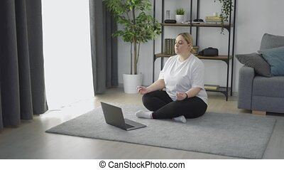 Relaxed overweight woman sitting in lotus pose on floor and meditating with closed eyes. Young blonde in sport clothes practising yoga and using laptop.