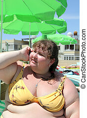 overweight woman on beach talking by phone
